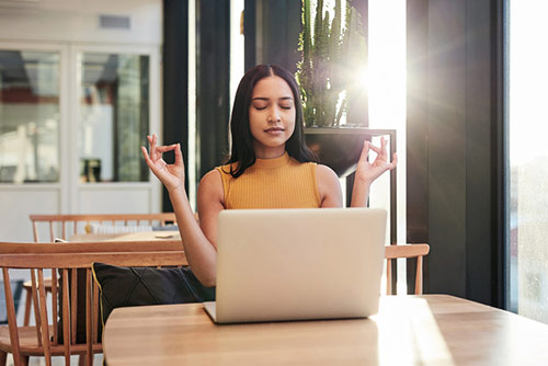 Woman meditating at her laptop